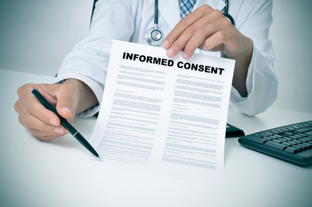 Photo pour a doctor in his office showing an informed consent document and pointing with a pen where the patient must to sign - image libre de droit