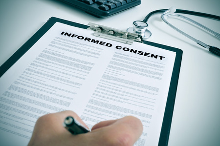 Photo pour patient signing an informed consent in a doctors office - image libre de droit