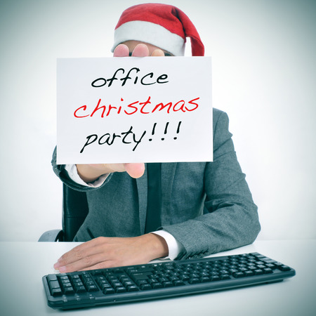 Foto de a man sitting in his desk with a santa hat holding a signboard with the text office christmas party written in it - Imagen libre de derechos