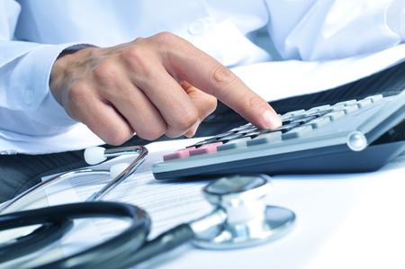 Photo for closeup of a young caucasian healthcare professional wearing a white coat calculates on an electronic calculator - Royalty Free Image
