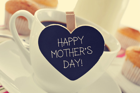 Photo for the sentence happy mothers day written in a heart-shaped blackboard placed in a cup of coffee, with some muffins in the background in a set table for breakfast - Royalty Free Image
