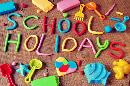 Photo pour the text school holidays made from modelling clay of different colors and some beach toys such as toy shovels and sand moulds, on a rustic wooden surface - image libre de droit