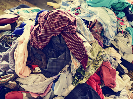 Photo pour closeup of a pile of different used clothes on sale in a flea market, with a filter effect - image libre de droit
