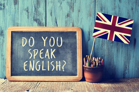 Photo for a chalkboard with the text do you speak english? written in it, a pot with pencils and the flag of the United Kingdom, on a wooden desk, with a filter effect - Royalty Free Image