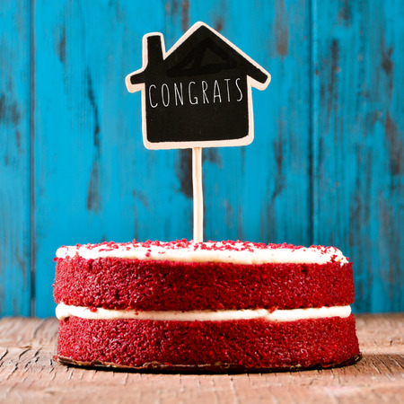 Photo for a red velvet cake with a chalkboard in the shape of a house with the text congrats, on a rustic blue wooden surface, with a retro effect - Royalty Free Image