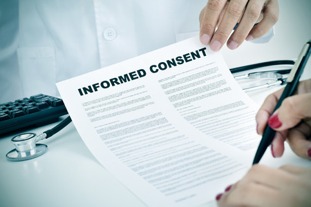 Photo for closeup of a young woman patient signing an informed consent at the doctors office - Royalty Free Image