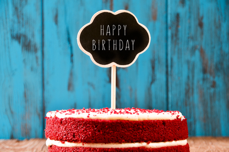 Foto de a red velvet cake with a chalkboard in the shape of a thought bubble with the text happy birthday, on a rustic blue wooden surface, with a retro effect - Imagen libre de derechos