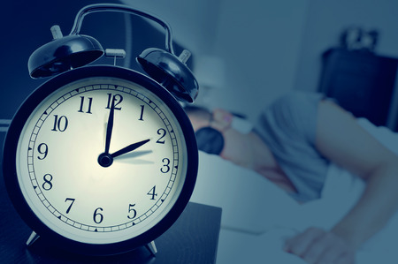 Photo pour closeup of an alarm clock on a nightstand adjusting backward one hour at the end of the summer time, while a young man sleeps in bed - image libre de droit