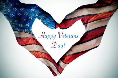 Photo for the text happy veterans day and the hands of a young woman forming a heart patterned with the flag of the United States - Royalty Free Image