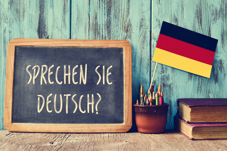 Photo for a chalkboard with the question sprechen sie deutsch? do you speak german? written in german, a pot with pencils, some books and the flag of Germany, on a wooden desk - Royalty Free Image