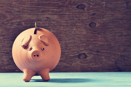 Foto de an earthenware piggy bank with a coin in his hole, on a blue rustic surface - Imagen libre de derechos