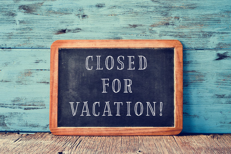 Foto de a wooden-framed chalkboard with the text closed for vacation written in it, on a rustic wooden surface, against a blue wooden background - Imagen libre de derechos