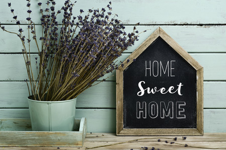 Photo for closeup of a house-shaped chalkboard with the text home sweet home written in it and a bunch of lavender flowers in a flower pot, against a rustic pale blue background - Royalty Free Image