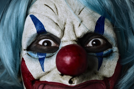 Photo for closeup of a scary evil clown wearing a blue hair wig - Royalty Free Image