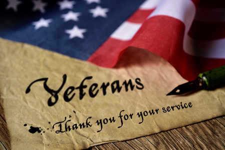 Photo for the text veterans than you for your service written in a piece of paper with a nib pen and a flag of the United States, on a rustic wooden background - Royalty Free Image