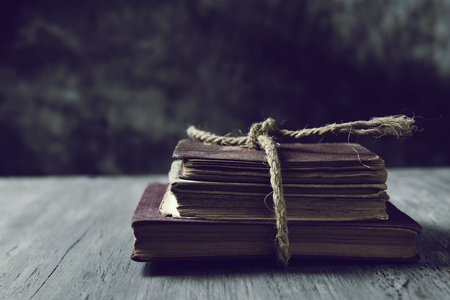 Photo for a pile of old books tied with a jute string on a rustic wooden table - Royalty Free Image