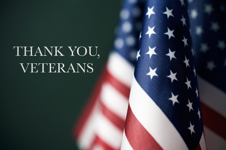 Foto de some american flags and the text thank you veterans against a dark green background - Imagen libre de derechos