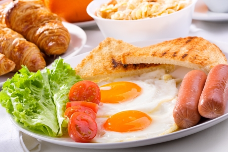 Photo for breakfast with fried eggs, sausages, tomatoes and toasts - Royalty Free Image