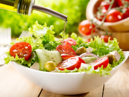 Photo pour olive oil pouring into bowl of salad - image libre de droit