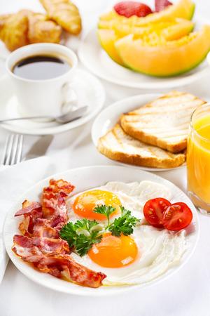 Photo pour Breakfast with fried eggs, coffee, orange juice, croissant, toasts  and fruits - image libre de droit