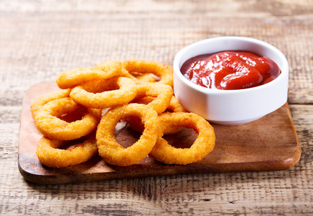 Photo pour onion rings with ketchup on wooden board - image libre de droit