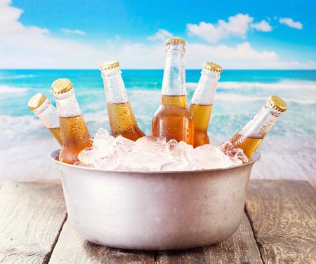Foto de cold bottles of beer in bucket with ice over sea - Imagen libre de derechos