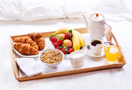 Photo for breakfast in bed. Tray with coffee, croissants, cereals and fruits - Royalty Free Image