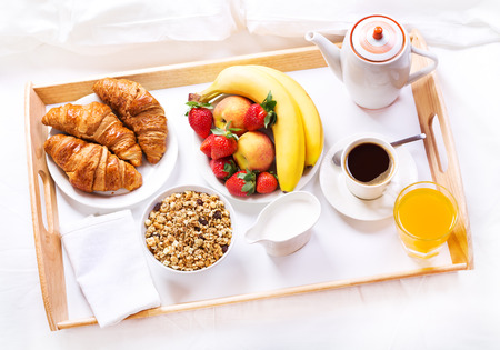 Photo pour Breakfast in bed. Tray with coffee, croissants, cereals and fruits - image libre de droit