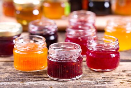 Foto de various jars of fruit jam on wooden table - Imagen libre de derechos