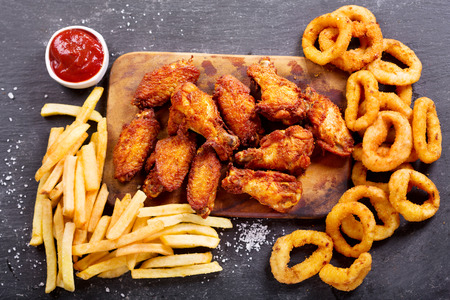 Photo pour fast food products : onion rings, french fries and fried chicken on dark table, top view - image libre de droit