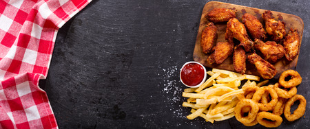 Photo for fast food products : onion rings, french fries and fried chicken on dark table, top view - Royalty Free Image