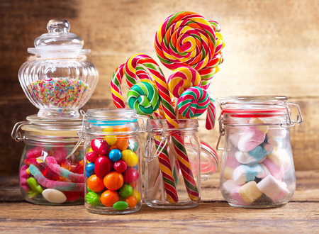 Photo for Colorful candies, lollipops and marshmallows  in a glass jars on wooden table - Royalty Free Image