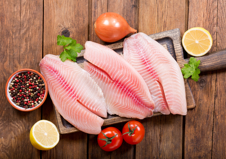 Foto de fresh fish fillet with ingredients for cooking, top view - Imagen libre de derechos