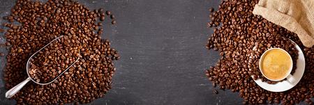 Foto de cup of coffee and coffee beans in a sack on dark background, top view - Imagen libre de derechos