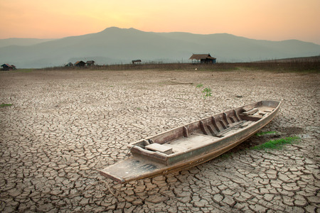 Photo for The wood boat on cracked earth, metaphoric for climate change and global warming. - Royalty Free Image