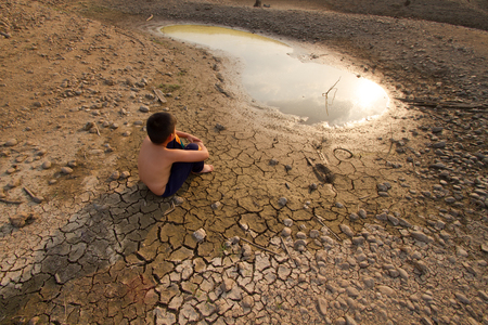 Photo pour Water crisis, Child sit on cracked earth near drying water. - image libre de droit