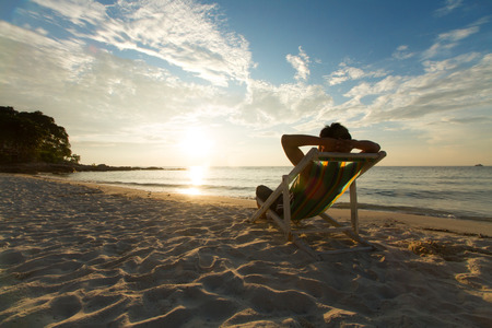 Foto de Man relax on chair beach in vacations with sunset and blue sky background. - Imagen libre de derechos