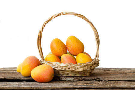 Mango tropical fruit in basket on wood desk isolated white background