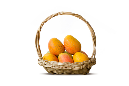 Mango tropical fruit in wooden basket isolated white background