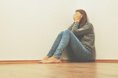 Sad girl hiding in corner at home