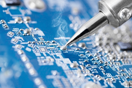 Foto de Microcircuit being fixed with soldering iron - very sharp micro photo - Imagen libre de derechos
