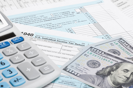 Photo pour Tax Form 1040 with calculator and US dollars - image libre de droit