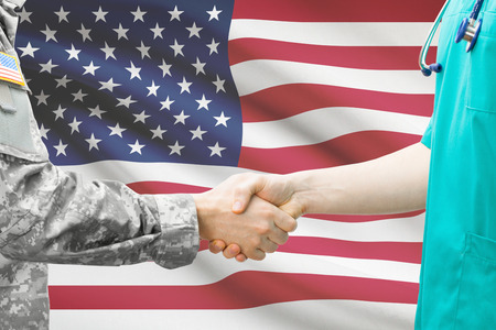 Foto de Soldier and doctor shaking hands with flag on background - United States - Imagen libre de derechos