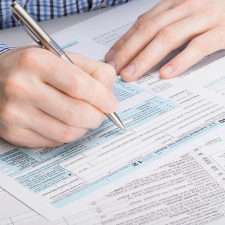 Photo pour US 1040 Tax Form - male filling out USA tax form - image libre de droit