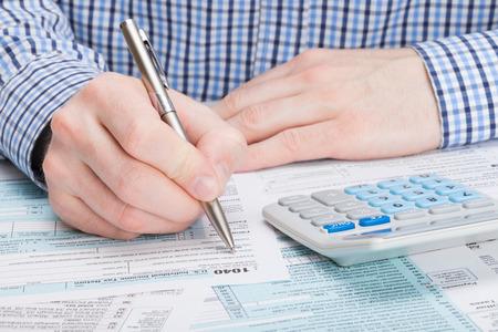 Photo pour Taxpayer filling out 1040 Tax Form - image libre de droit