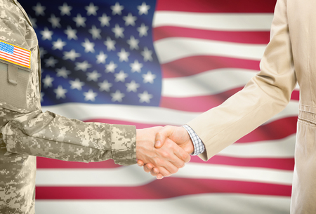 Foto de American soldier in uniform and civil man in suit shaking hands with national flag on background - United States - Imagen libre de derechos