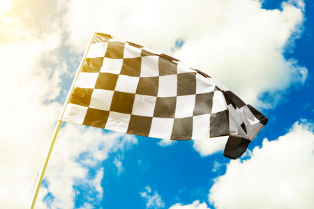 Photo pour Checkered flag waving in the wind with sun flare visible - image libre de droit