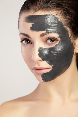 Foto de Young beautiful woman in a mask for the face of the therapeutic black clay. Spa treatment. - Imagen libre de derechos