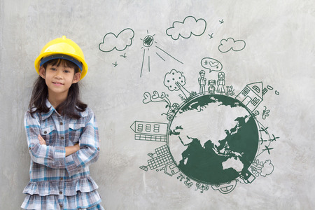 Foto de Little girl engineering with creative drawing on world map environment with happy family, eco friendly, save energy, against a brick wall - Imagen libre de derechos