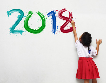 Photo for little girl holding a paint brush painting happy new year 2018 on a white wall background - Royalty Free Image